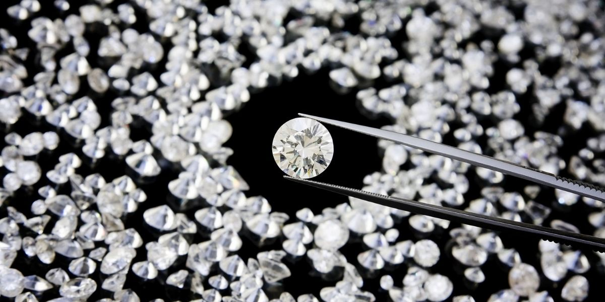 A jeweler selecting a diamond from a melee parcel