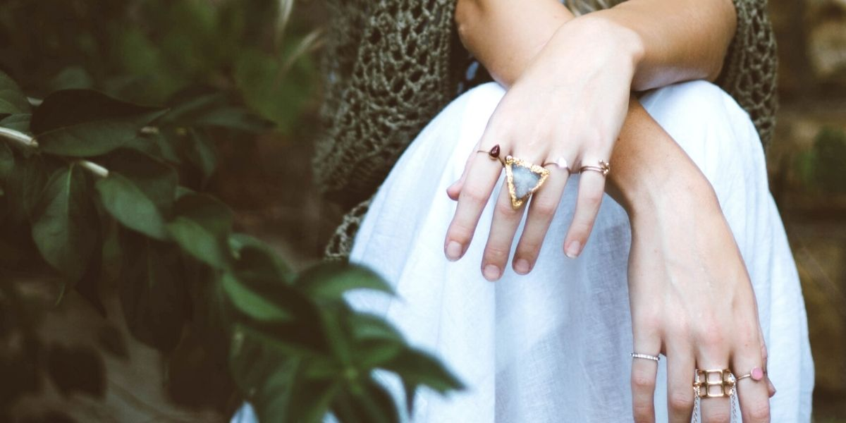 A woman wearing multiple rings, representing a large inventory. Moving to on-demand production is one of the best ways to improve efficiency in your jewelry business.