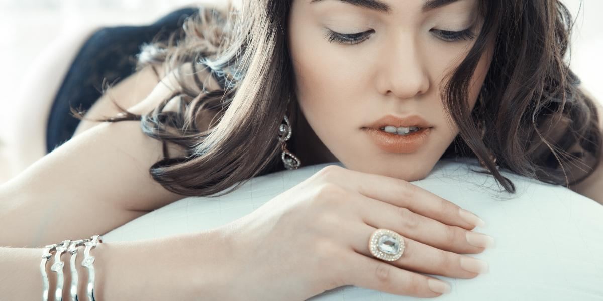 A woman gazing at a sentimental ring while wondering about insuring jewelry